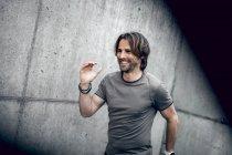 Smiling athlete exercising at concrete wall — Stock Photo
