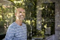 Portrait of smiling mature man behind windowpane at home — Stock Photo