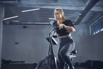 Athletic woman doing airbike workout at gym — Stock Photo
