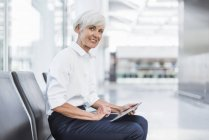 Smiling senior businesswoman sitting in waiting area and using tablet — Stock Photo