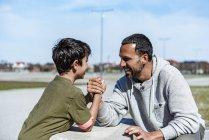 Отец и сын армрестлинг на открытом воздухе — стоковое фото