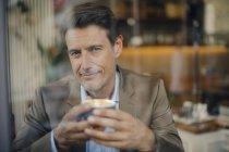 Зрелый бизнесмен, сидящий в кафе, улыбающийся — стоковое фото