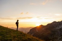 Man standing in mountains at sunset — Stock Photo