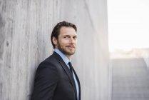 Ritratto di uomo d'affari sicuro al muro di cemento — Foto stock