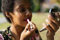 Retrato de mulher jovem aplicando batom ao ar livre — Fotografia de Stock