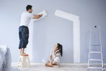 Couple painting house shape on wall in new apartment — Stock Photo