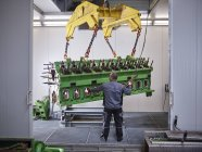 Worker in factory lifting engine block with crane — Stock Photo