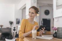 Junge Frau arbeitet im Coworking Space mit digitalem Tablet — Stockfoto