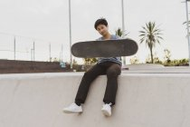 Молодой китаец сидит на стене скейт-парка рядом с пляжем — стоковое фото