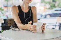 Giovane donna seduta in caffetteria e bere tè — Foto stock