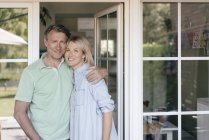 Portrait of smiling mature couple standing at French window — Stock Photo