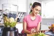 Портрет улыбающейся молодой женщины с помощью планшета на кухне за столом с блендером и фруктами — стоковое фото