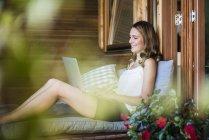 Улыбающаяся женщина отдыхает на балконе и пользуется ноутбуком — стоковое фото
