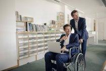 Un collega che spinge un uomo d'affari, seduto a Wheelchai? — Foto stock
