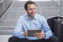 Lächelnder Geschäftsmann mit rollendem Koffer sitzt mit Tablet auf Treppe — Stockfoto