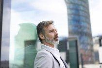 Espanha, Barcelona, empresário pensativo encostado à fachada de vidro — Fotografia de Stock