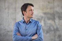 Empresário na frente da parede de concreto olhando para os lados — Fotografia de Stock