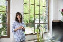 Mujer de pie en la ventana de su apartamento loft, bebiendo café - foto de stock