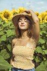 Jovem mulher segurando chapéu de palha na cabeça em um campo de girassóis — Fotografia de Stock