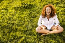 Portrait of happy young woman with tablet relaxing on green meadow — Stock Photo