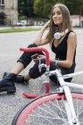 Усміхнена Дівчинка-підліток сидить вниз Холдинг стільниковий телефон поруч з велосипеда — стокове фото