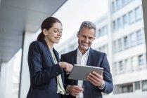 Портрет двух бизнес-партнеров, смотрящих вместе за планшетом — стоковое фото