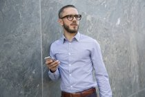 Geschäftsmann mit Handy im Freien schaut zur Seite — Stockfoto