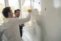 Homem de negócios maduro compartilhando seu conhecimento com colega mais jovem — Fotografia de Stock
