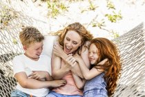 Happy mother with children in hammock — Stock Photo