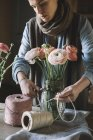 Woman arranging fresh flowers, cutting cord — Stock Photo