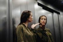 Junge Frau blickt in Spiegel im Aufzug und pustet einen Kuss — Stockfoto