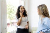Двое друзей дома, делают телефонный звонок — стоковое фото