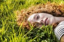 Портрет рыжей молодой женщины, лежащей на зеленой траве — стоковое фото