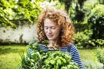 Портрет молодой рыжей женщины со свежими травами в саду — стоковое фото