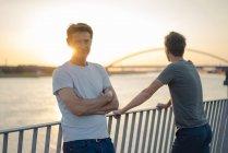 Zwei Freunde beobachten den Sonnenuntergang am Fluss — Stockfoto