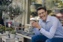 Зрелый бизнесмен, сидящий в кафе, пьющий кофе — стоковое фото