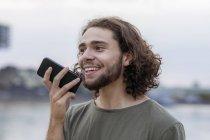 Молодой человек с помощью смартфона на берегу реки — стоковое фото