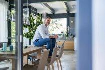 Улыбающийся взрослый мужчина сидит дома за столом с чашкой кофе — стоковое фото