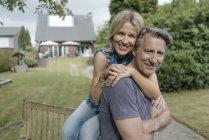Портрет улыбающейся зрелой пары, обнимающейся в саду дома — стоковое фото