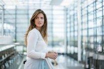 Junge Frau steht am Geländer und schaut sich um — Stockfoto