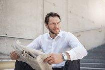 Empresário sorridente sentado nas escadas lendo jornal — Fotografia de Stock