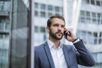 Young businessman on cell phone looking sideways — Stock Photo