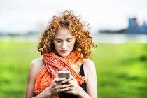 Портрет молодой женщины с вьющимися рыжими волосами с помощью мобильного телефона на открытом воздухе — стоковое фото