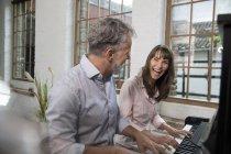 Зріла пара бавиться вдома, грає на піаніно. — стокове фото