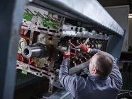 Роботодавець на заводі ремонтує двигун. — стокове фото
