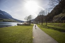 Autriche, Tyrol, Walchsee, fille qui court sur le chemin du lac — Photo de stock