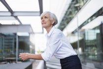 Вдумчивый пожилая женщина, опираясь на перила в городе — стоковое фото