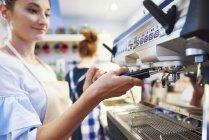 Женщина-бариста готовит кофе в кафе — стоковое фото