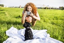 Portrait of smiling young woman on meadow taking picture of dog on green meadow — Stock Photo
