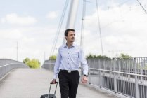 Businessman with rolling suitcase crossing a bridge — Stock Photo